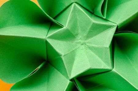 Abstract closeup of a green paper origami flower with star shape in the middle. Top view.