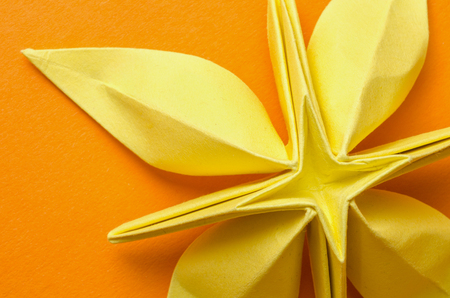 Abstract closeup of a yellow paper origami flower with petals and a cross shape in the middle on orange background. Top view. Фото со стока