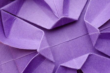 Abstract closeup of a purple paper origami flower. Top view. photo