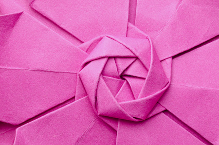 Abstract closeup of the intricate central radial part of a pink paper origami flower. Top view. photo