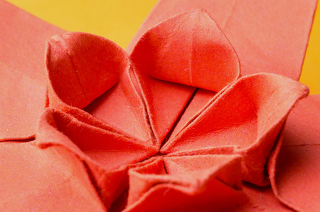 Abstract macro of a red paper origami cherry blossom flower on orange background. Side view. photo
