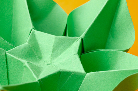 Abstract closeup of a green paper origami flower with star shape in the middle on orange background. Side view. photo
