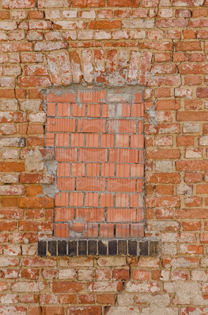 impediment: window closed with bricks in an old exterior grungy wall