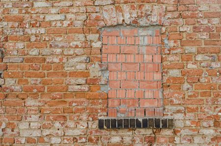impediment: window closed with bricks in an old grungy brick wall