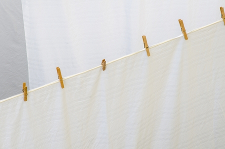 white washed: close-up of a line of wooden pins holding a white washed sheet on a rope Stock Photo