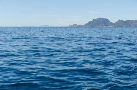 stretch out: detailed sea water surface and waves stretch out to the horizon where mysterious islands are visible far away on a clear sunny day