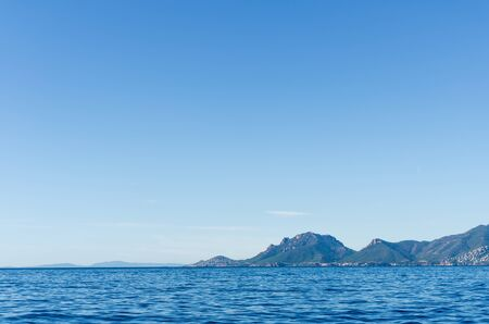 far away: mysterious islands visible far away on the horizon in the sea on a clear sunny day Stock Photo