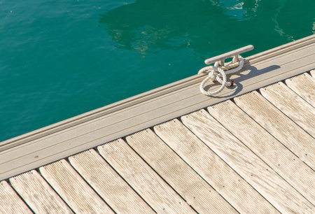 cleat: cleat hitch on the dock of the wooden pier at sea on a sunny day