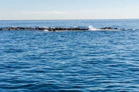 water waves: waves crushing into far away rocks in the middle of the sea water surface with intricate wave pattern Stock Photo