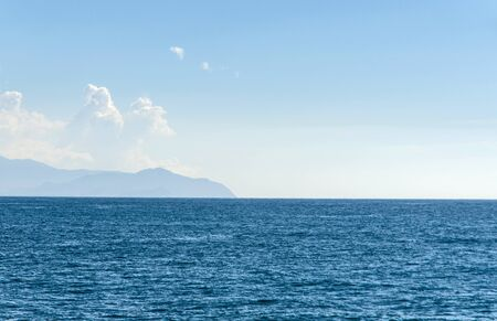 far away: islands with mountains visible far away through the haze on a beautiful sunny day on the sea
