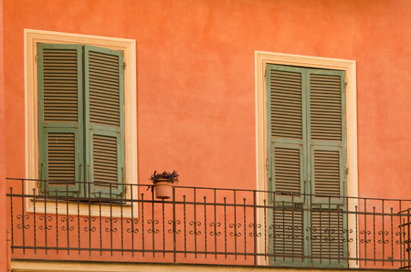 balcony door: old wooden shutters on the window and door leading to an exterior balcony of  mediterranean urban house Stock Photo