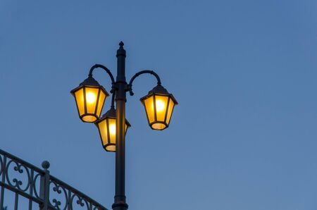 lamp light: vintage street lamp post glowing with wonderful wam orange light in front of a clear blue sky in the evening