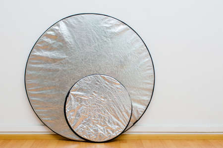 reflectors: two round silver reflectors against the white wall of a photo studio Stock Photo