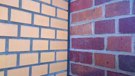 adjacent: two adjacent brick walls with different patterns and colors meeting in the corner