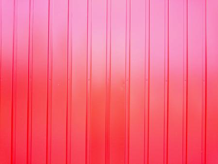 lineas verticales: pared de metal reflectante de color rojo con un patrón regular de líneas verticales Foto de archivo