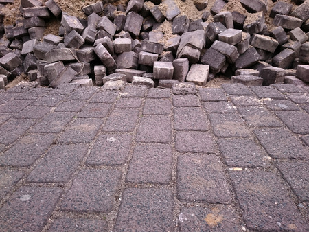 chaos order: regular brick pattern of the pavement merging into chaotic pattern of bricks thrown together in the distance Stock Photo