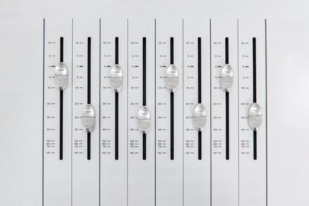 alternate: music mixer slider buttons on metallic casing forming an alternate pattern with small amplitude Stock Photo