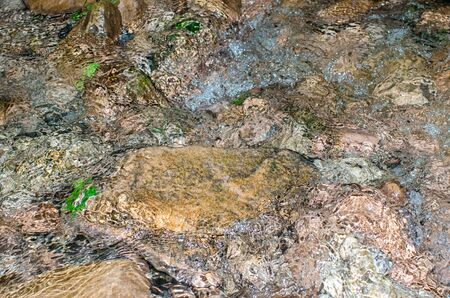 water frozen: shallow stream water frozen in motion over colorful underwater stones Stock Photo