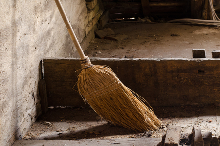 dusty: old broom in the dusty weathered room of a house Stock Photo