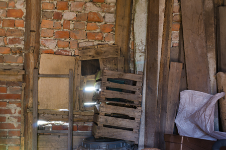 fractures: light shinning through the fractures in the old barn brick wall with wooden planks and crates leaning against it