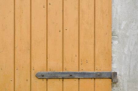 hinge: Background of old wooden door with rusty metal hinge in a cement wall