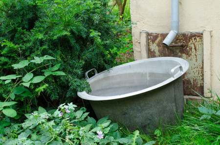 old metal bucket in the garden by the house under the rain gutter for collecting water