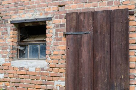 decaying: old wooden door and window in a weathered decaying house brick wall Stock Photo