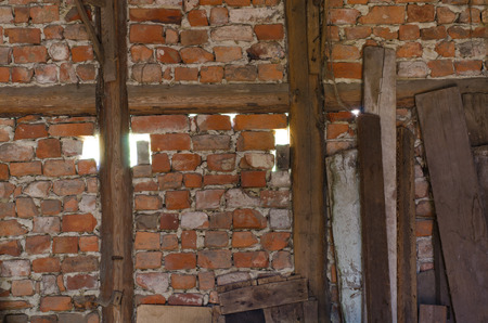 shinning light: light shinning through the gaps in the old brick wall with timber framing to the inside of a barn
