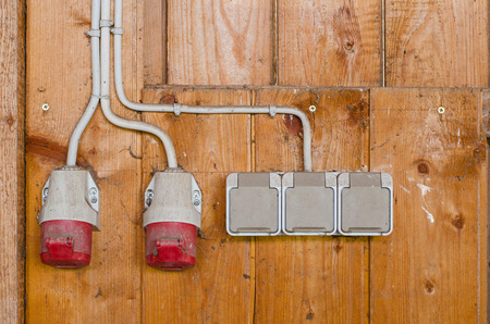 sockets: AC electrical power sockets including industrial high voltage sockets on a wooden wall