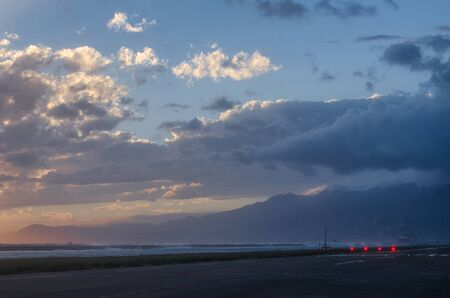 cloudy weather in the evening over the Apennine mountains seen from the landing strip at the Genoa airport