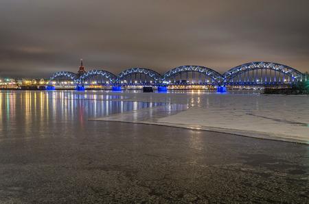 冬の夜に凍った川ダウガヴァ Riga, ラトビアの鉄道橋します。