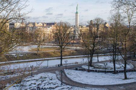 美しい冬の日に要塞の丘公園から、ラトビアのリガの自由の記念碑のビュー 写真素材