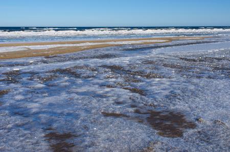 ユールマラ、冷たいバルト海に臨むリガ湾のリゾート町のビーチで美しい氷の表面