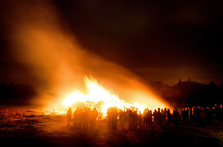 crowd silhouettes surrounding a huge burning Easter bonfire and celebrating as the night sets in the village