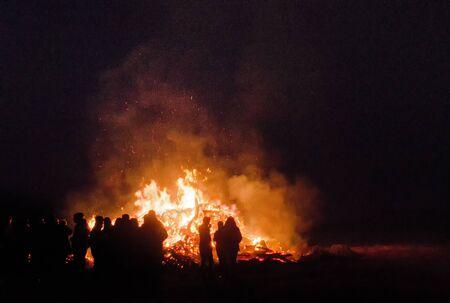 大きい人々 の群衆夜大きなイースターのたき火の前にシルエットとしてのみ表示 写真素材