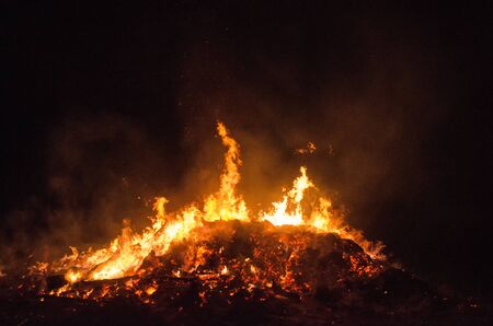 burning bonfire at night with flames reaching into the dark sky Stock Photo