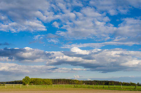 amazing cloudy sky over a rural landscape with forest and wooden fence on a sunny spring day 写真素材