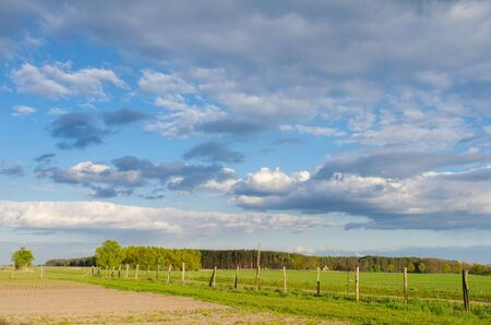 old wooden fence leading into the rural landscape with forest and cloudy sky on a sunny spring day