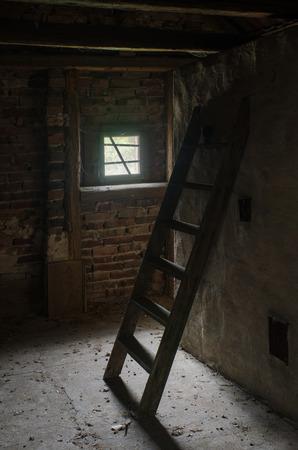 屋根裏部屋の小さな窓からの光に照らされた、忘れ去られた木製のはしご 写真素材