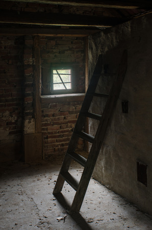 wooden ladder, long forgotten, illuminated by the light through a small window in the attic