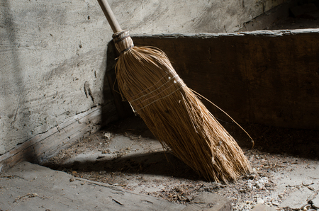 supposed: a broom abandoned long ago collecting dust it is supposed to clean