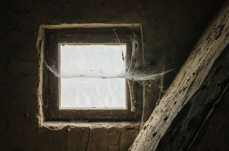 spiders web crossing an old window in a rustic room made of stone 写真素材