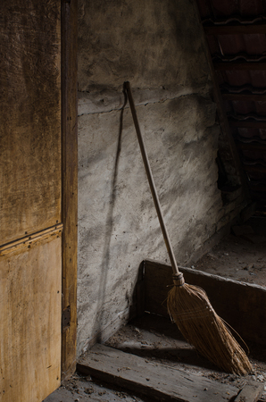 屋根裏部屋で古いほうき 写真素材