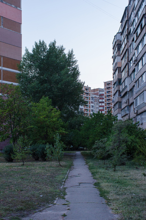 small path leading up to an old soviet era residential buildings framing the trees below them in Kiev, Ukraine, during the blue hour in summer 写真素材