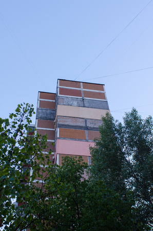 side view of one of the soviet era residential buildings in Kiev, Ukraine, with its interesting anch charachteristic architectural patterns towering over the tree tops during the blue hour