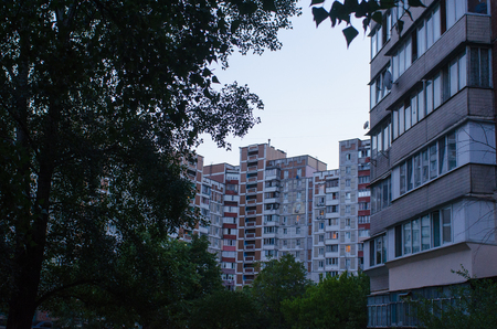 a blue hour frame made of tree silhouettes and residential buildings in Kiev, Ukraine
