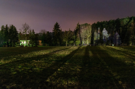 strangely illuminated natural rural landscape with a single house full of light and life in this dark evevning scenery