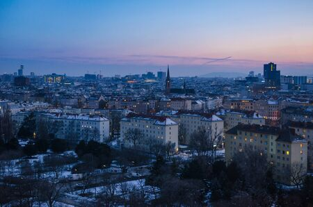 A winter evening sets over Vienna as the sun disappears and the many windows of the city begin to light up 写真素材