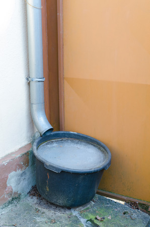 bucket collecting rain water near at a rural house completely frozen in winter