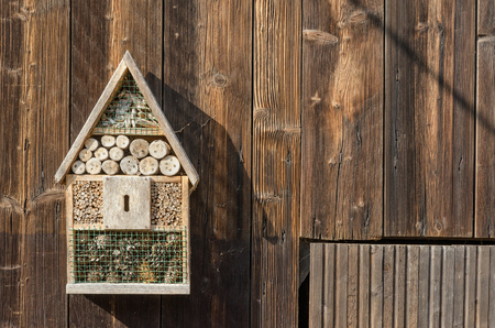 an old insect hotel hanging on a wooden barn door in the countryside